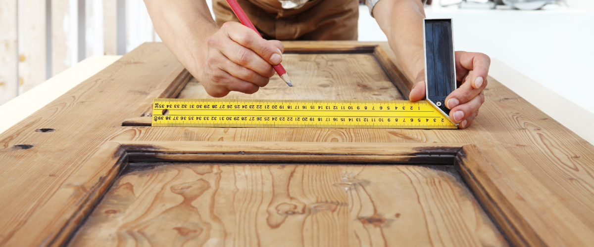 Carpenter At Work Measures With The Setsquare And Pencil On Wooden Board Background